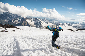 The tired traveler descends from the snowy top against the background of snow-capped mountains