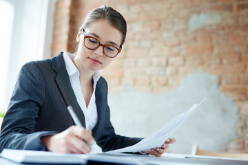 Young pretty accountant in eyeglasses and suit writing down her working ideas in notebook