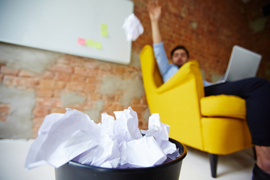 Modern freelancer throwing crumpled paper into trash bin
