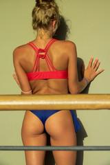 Stupenda ragazza giovane capelli biondi bikini bicolore posa su muro giallo molto sensuale con fisico perfetto