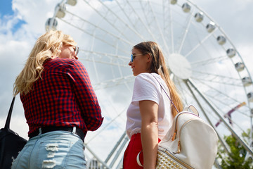 Two friendly girls standing by ferry in amusement park and deciding where to go