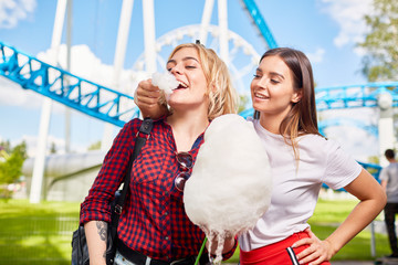 Happy girls eating cotton-candy in theme park on summer day