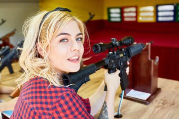 Cute teenage girl with rifle shooting at festival tent in amusement park