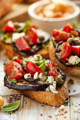 Bruschetta with grilled aubergine, cherry tomatoes, feta cheese, capers and fresh aromatic herbs, on a wooden table. Delicious Mediterranean appetizer