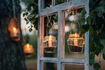 Lamps  with candles  are  hanging  on a tree at night. Wedding night decor.