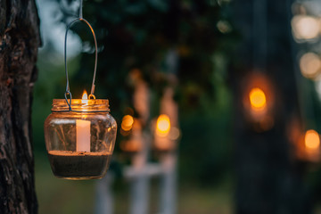 Lamp  with candle  is  hanging  on a tree at night. Wedding night decor.