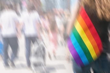 Conceptual blurred picture of gay rainbow flag with gay male couple in background. Concept of LGBT rights.