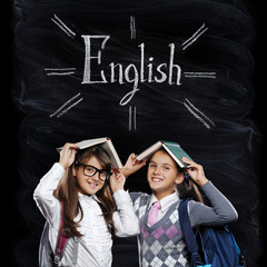 Two schoolgirls holding books as house roofs on chalkboard  background with a word English