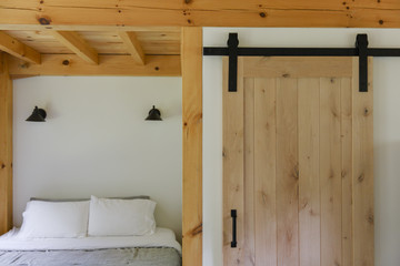 USA, Vermont. Bedroom and bathroom door in a design house. A lot of wooden elements are used in the newly built cabin.