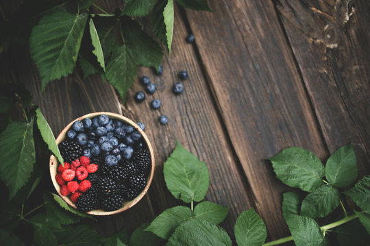 Bowl of freshly picked berries over wooden table and greenery