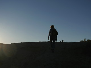 Female backpacker climbing up the hill