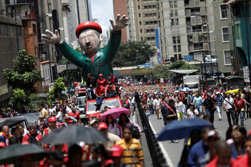 Pro-government supporters carrying a giant inflatable doll of Venezuela's late President Chavez attend a rally against U.S President Trump in Caracas