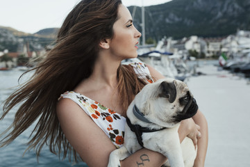 Young woman and her pug dog Max by the sea