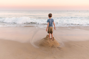 Boys standing on sandcastle waiting for the sea to destroy it