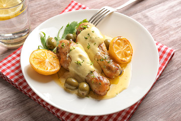 Delicious chicken legs with lemon on plate