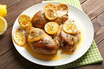 Delicious chicken breasts with lemon on plate