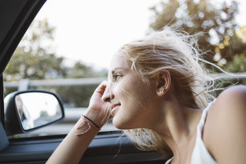 Young happy woman traveling by car