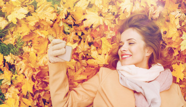 woman on autumn leaves taking selfie by smartphone