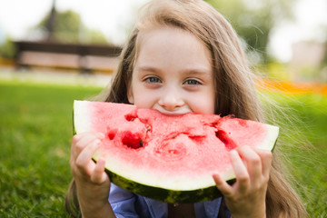 Happy  adorable little girl laying on grass eating watermelon in summertime.Happy little girl  Having Fun outdoors in summer.