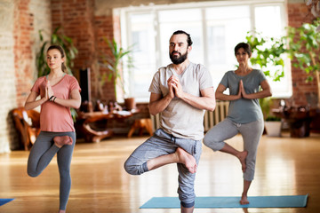 group of people doing yoga tree pose at studio