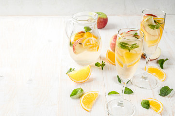 Drinks and cocktails. White autumn sangria with apples, orange, mint and white wine. In glasses for champagne, in a pitcher, on a white wooden table. Copy space