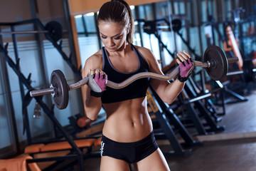 Młoda kobieta ćwiczy z ciężarem w gym.