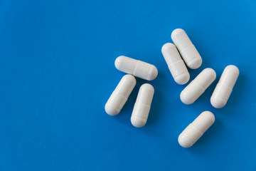 White pills on blue background