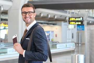 Businessman holding passport and boarding pass at the airport