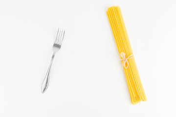 Fork With Raw Italian Spaghetti Pasta On White Background Closeup