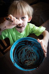 boy licking the Brownie mix in bowl with messy face