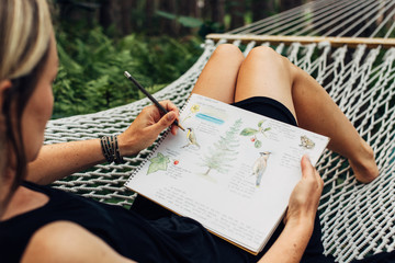 Woman in black dress drawing in her journal on a hammock