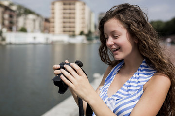Young woman taking pictures to her friends in the city