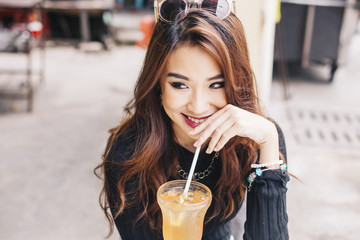 young asian woman having ice tea at a cafe