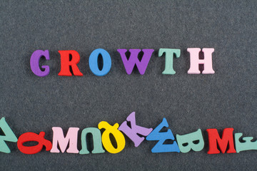 Growth word on black board background composed from colorful abc alphabet block wooden letters, copy space for ad text. Learning english concept.