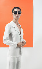 Fashionable model with sunglasses in front of white and orange background.
