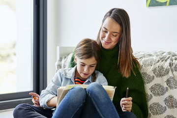 Woman Looking At Daughter Drawing In Book