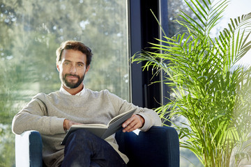 Confident Man With Book Sitting On Chair At Home