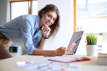 Beautiful young business woman sitting at office desk and talking on cell phone. Business woman