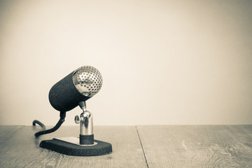 Old retro microphone from 50s on table. Vintage style sepia photo