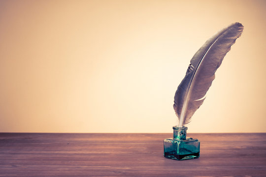 Vintage old quill pen, inkwell on wooden table. Retro style filtered photo