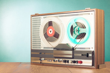 Retro reel to reel audio tape recorder on table in front turquoise background. Old instagram style filtered photo