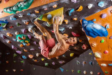 Young man bouldering in indoor climbing gym, solving challenging problem