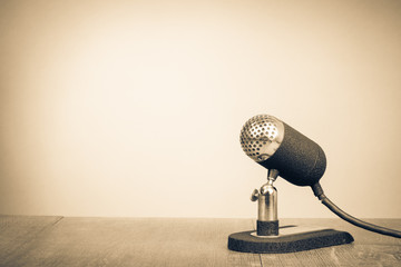 Retro old microphone from 50s on table. Vintage style sepia photo