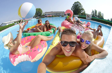 SELFIE: Smiling young people enjoying on fun colorful floaties, playing volleyball at pool party. Happy teenagers on inflatable pizza, flamingo, watermelon and doughnut floats having watergun fight