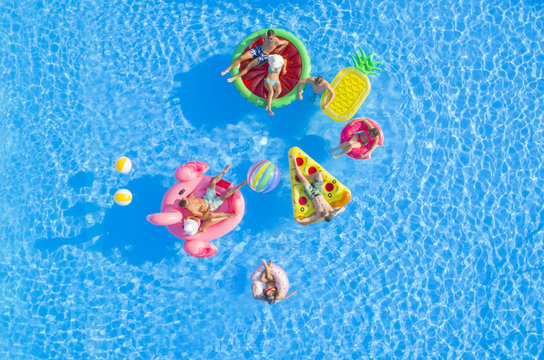 AERIAL TOP DOWN COPY SPACE Fit girls and muscular guys lying on colorful floaties in pool, relaxing and hanging out on the sun. Friends on fun summer vacation floating on water on inflatable pillows