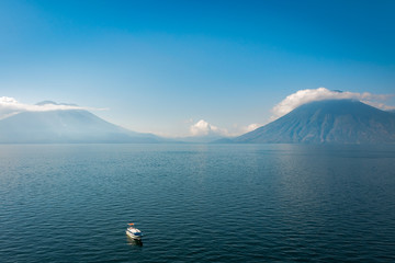 Simple but stunning panoramic view of Lake Atitlan and Volcanoes San Pedro and Toliman in Guatemala, from above with a small touristic boat in foreground.