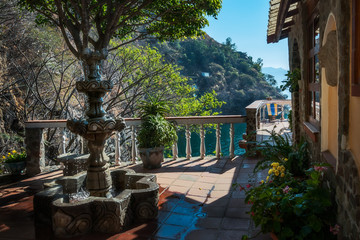 Picturesque terrace with a fountain and flower pots of a secluded resort at Lake Atitlan in Guatemala.