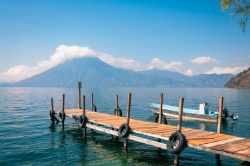 Astounding View of Volcano San Pedro with a crown of clouds from the shore of Lake Atitlan in Guatemala with a tourist boat docked at a pier.