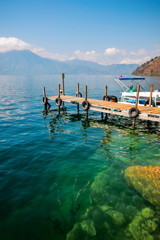 The boardwalk pier out into the crystal-clear waters of Lake Atitlan in Guatemala with Volcano San Pedro in the background.