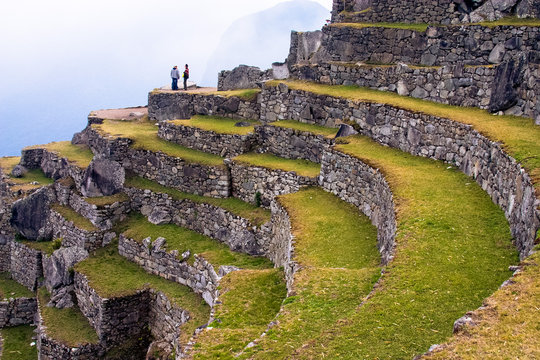 A couple of people standing on the terraces of the ancient inca village of Machu Picchu